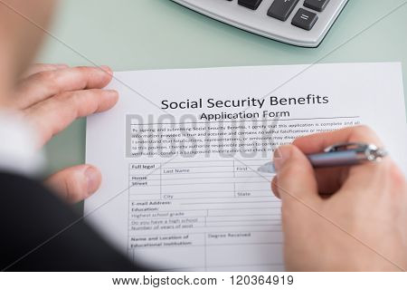 Close-up Of Person Hand Filling Social Security Benefits Form poster
