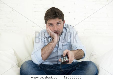 young bored man watching tv sitting at home living room sofa looking tired and not having fun with the television program or movie using remote control for changing to another channel