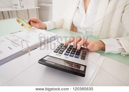 Close-up Of Businesswoman Checking Bill With Magnifying Glass
