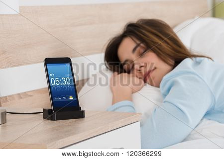 Woman Sleeping On Bed With Alarm On Mobile Phone