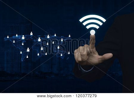 Businessman Pointing To Wi-fi Button With Light Blue World Map Connection On City Tower, Technology