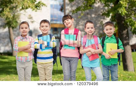 childhood, preschool education, learning and people concept - group of happy smiling little children with school bags and notebooks over summer campus background