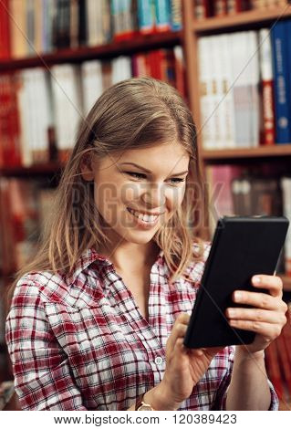 Smiling merchant with iPad tablet in book store or library.