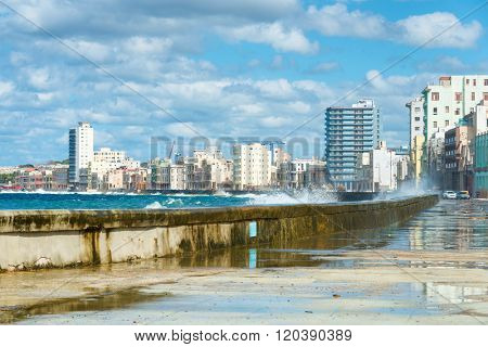 The Havana skyline with big sea waves crashing on the Malecon seawall