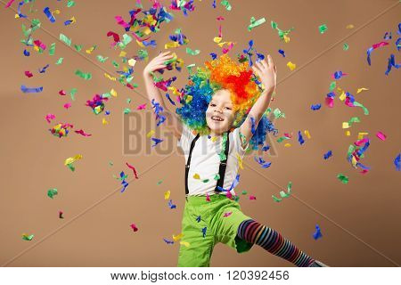 Little Boy In Clown Wig Jumping And Having Fun Celebrating Birthday.
