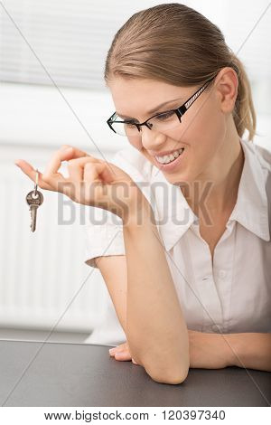 Woman looking at a key of new house at realtor's office