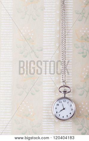 old pocket watch on the vintage wallpaper background