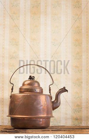 antique vintage copper kettle on the background of old wallpaper