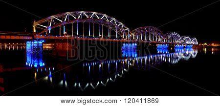 Night panorama of Riga, Latvia with illuminating railway bridge reflecting in Daugava river