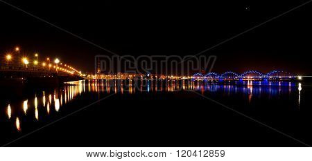 Night Panorama of Riga with colourful illumination reflecting in Daugava River