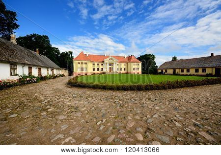 Yellow classicism style mansion in Durbe, Latvia. Historical Russian Empire building.
