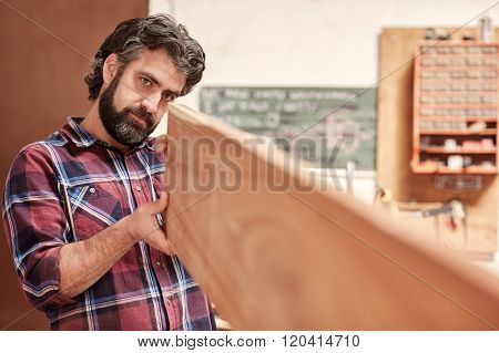 Craftsman in his workshop looking down length of wooden plank