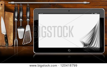 Black tablet computer with blank pages in a kitchen on wooden wall with kitchen utensils. Template for recipes or food menu