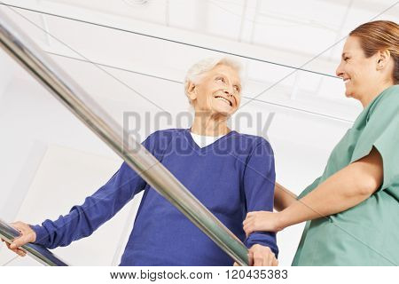 Smiling old woman in physiotherapy on a treadmill with physiotherapist