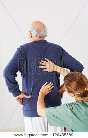 Physiotherapist laying hands on senior man with back pain in physical therapy
