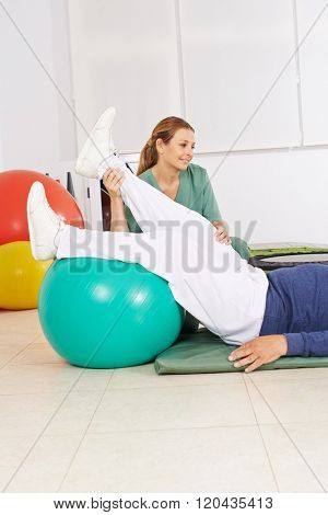 Physiotherapist holding leg of old man during physical therapy