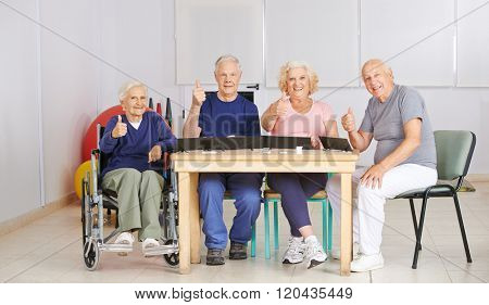 Group of senior people holding thumbs up and playing a game in nursing home