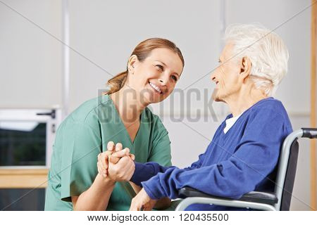 Happy geriatric nurse holding hands with senior woman in a wheelchair
