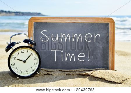 an alarm clock and a chalkboard with the text summer time on the sand of a beach