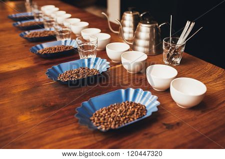 Rows of cups, glasses and containers with coffee beans