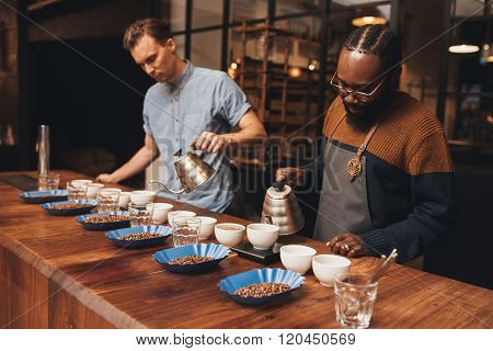 Two baristas preparing a coffee tasting in roastery