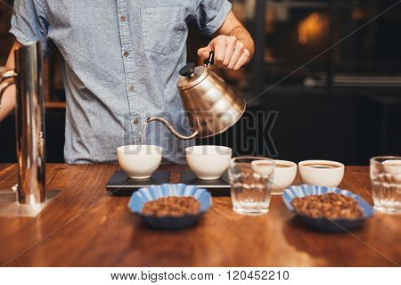Man pouring water into coffee cup on a digital scale