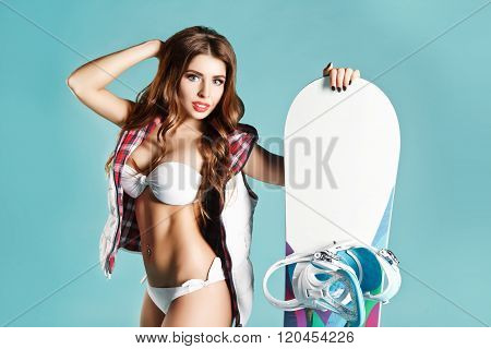 Portrait Of Pretty Young Sexy Girl In Bikini Holding White Snowboard On Blue Background. Space For Y