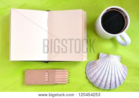 Notebook shell cup of coffee and pastels on green background (flat lay)