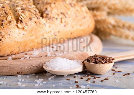 Two Spoons With Salt And Flax Seeds Next To Bread