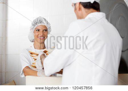 Female Baker Receiving Bread Waste From Male Colleague