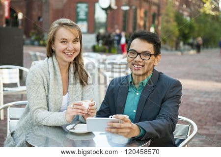Two smiling young people with mobile device while sitting at outdoor cafe table on city street