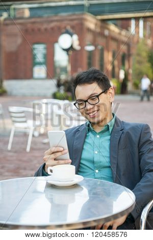 Successful young asian man in business casual attire sitting and smiling in relaxing outdoor cafe with cup of coffee looking at mobile device