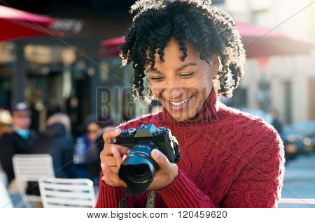 Portrait of african tourist with digital camera at cafe. Joyful woman looking at pictures on digital camera sitting outside the cafetria. American woman taking picture photo with camera ih holiday.