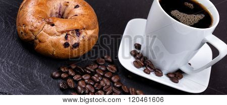 Roasted Coffee Beans With Drink And Bagel In Background On Slate Stone