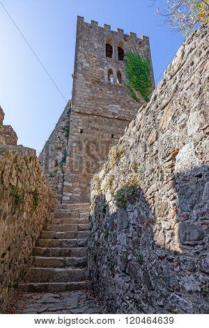 Bell Tower ruins of the medieval Nossa Senhora da Pena Church (aka Santa Maria da Pena) in the Castle of Leiria, seen from a narrow passage. Leiria, Portugal.