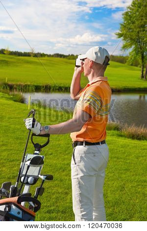 man golfer watching into rangefinder
