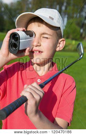 boy golfer watching into rangefinder