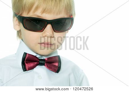 Portarit of small gentleman special agent boy with blonde hair in white shirt red formal bow tie and sun glasses indoor on light background horizontal picture poster