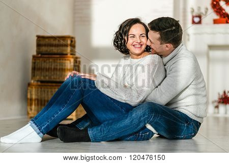 Beautiful young loving couple sitting together on the couch while man embracing his girlfriend and s