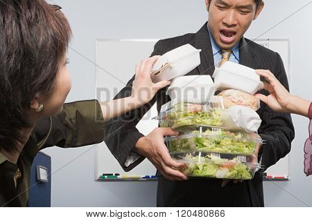 People taking food from colleague