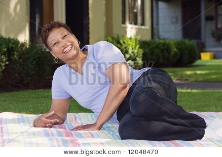 Middle-aged woman relaxing on a picnic blanket
