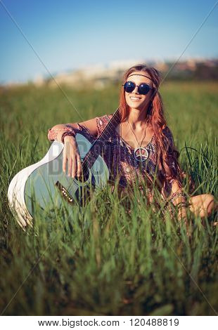 Portrait Of Beautiful Smiling Hippie Woman With Guitar In The Field