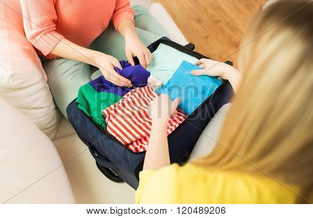 trip, vacation, luggage and people concept - close up of young woman or teenage girl packing clothes into travel bag poster