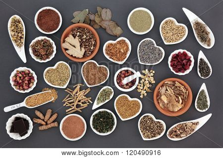 Health food with herb and spice selection for womens health over grey background.