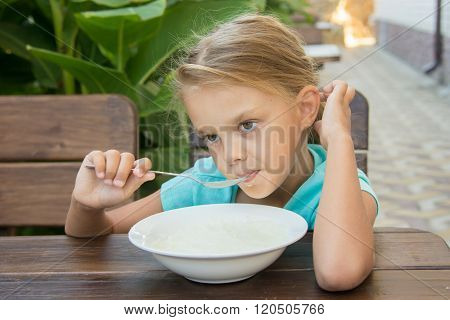 Upset Six Year Old Girl Slowly Eating Porridge For Breakfast