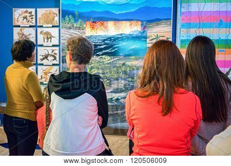 Listvianka, Russia - February 15, 2016: Rear View Of People Looking Prehistoric Trees And Dinosaurus