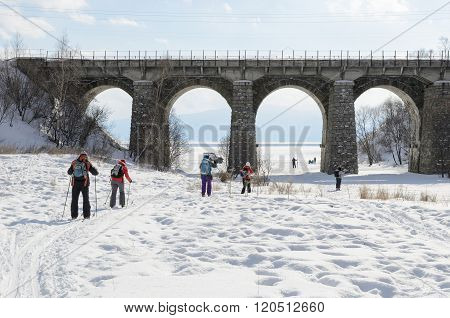 Irkutsk Region, Russia-Feb 27, 2016:Tourists-skiers go under Circum-Baikal Railway bridge