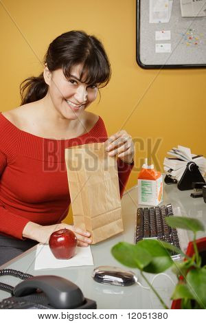 Happy businesswoman with lunch bag