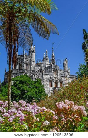 Sintra, Portugal - July 14, 2015: Regaleira Palace seen through the Gardens. A neo-manueline palace decorated with alchemy and freemasons symbols.
