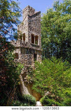 Sintra, Portugal - July 14, 2015: Stone Tower in the Mundos Celestes Terrace at Regaleira Palace and Gardens. A neo-manueline palace decorated with alchemy and freemasons symbols.